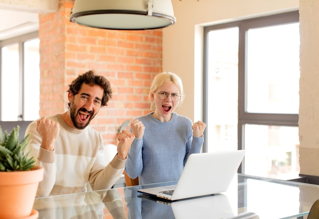 Couple shouting aggressively with an angry expression or with fists clenched celebrating success