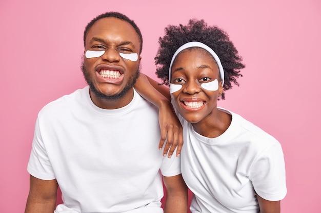 Пара демонстрирует идеальные белые зубы. проводите время вместе на косметических процедурах. наденьте повседневные футболки. нанесите подушечки под глаза для увлажнения, изолированные на розовой стене.