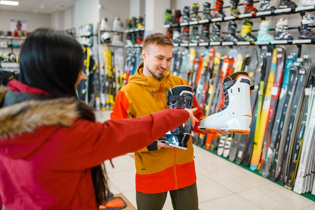 Couple at the showcase choosing ski or snowboarding boots, shopping in sports shop