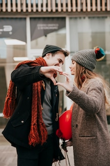 Couple showing heart gesture before kiss