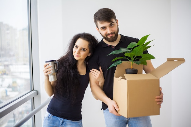 Couple showing keys to new home hugging looking at camera