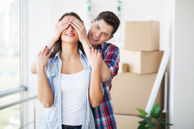 Couple showing keys to new home hugging, together unpacking cardboard boxes