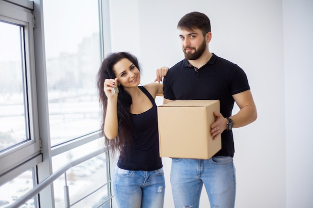 Couple showing keys to new home hugging