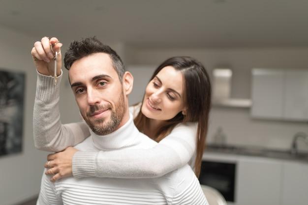 彼らの新しい家の鍵を示すカップル