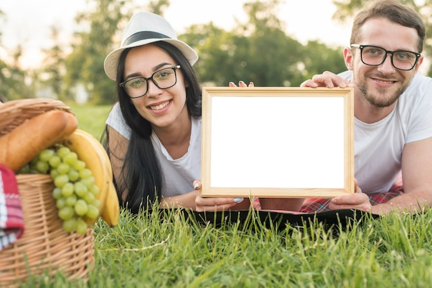 Couple showing a whiteboard on a picnic blanket