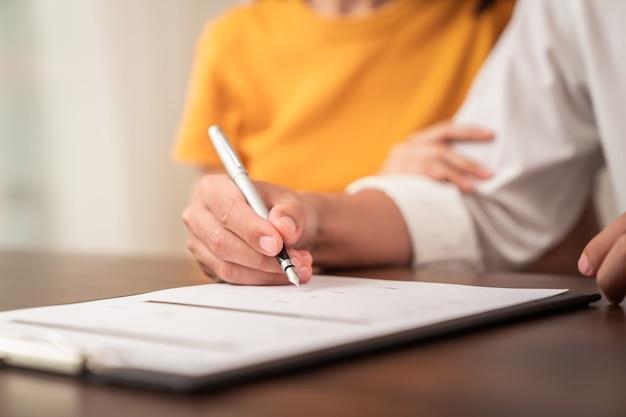 合意に達した後、カップルの署名文書と手持ちのペンパッティング署名。