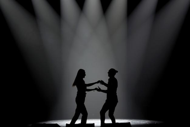 Couple in silhouette dancing salsa, latin dance,