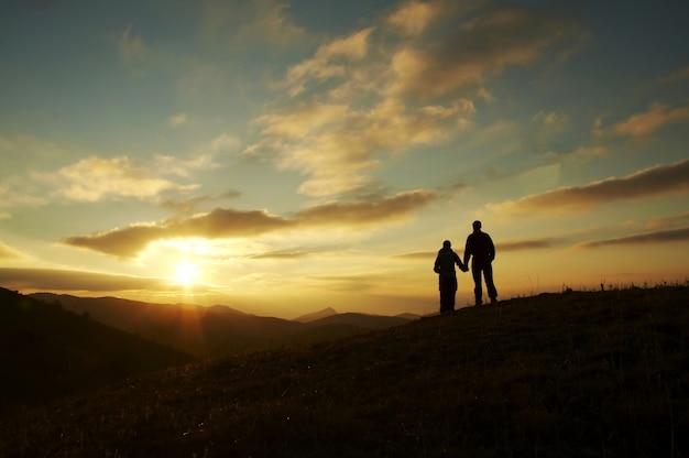 夕日の背景にカップルのシルエット
