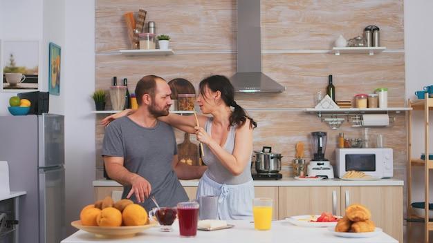 朝の朝食時にパジャマを着てキッチンで歌うカップル。のんきな妻と夫が笑って楽しんで面白い人生を楽しんでいる本物の既婚者ポジティブ幸せな関係