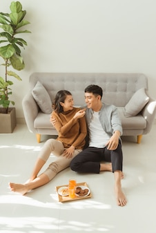 Couple sit on living room floor together eating