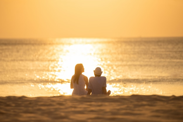 Couple sit on sand looking sunset in sea together.