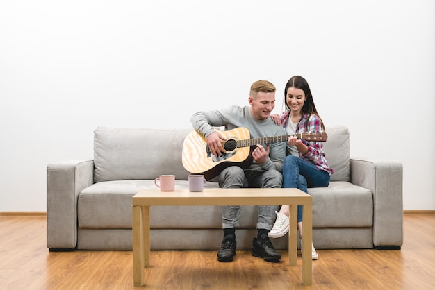 The couple sit on the sofa and play the guitar on the white wall background