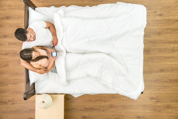 The couple sit with a phone on the bed. view from above