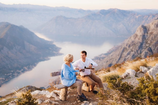 커플은 벤치에 앉아 lovcen 산과 kotor만을 배경으로 차를 마신다.