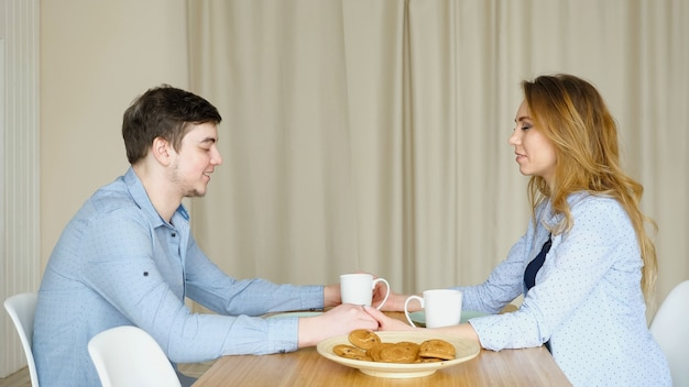 Couple sits at table join hands and pray before breakfast