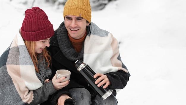 Пара сидит и пьет горячие напитки высокого зрения