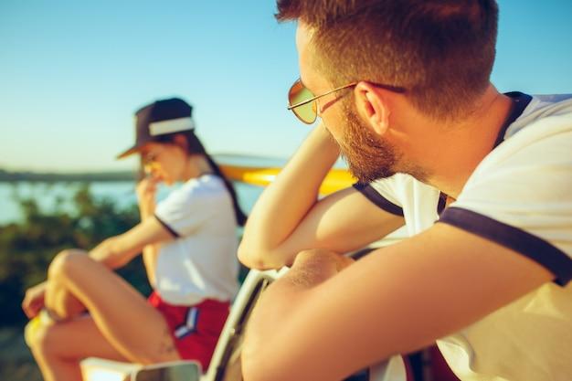 川の近くの夏の日にビーチに座って休んでいるカップル