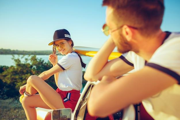 川の近くの夏の日にビーチに座って休んでいるカップル。白人の男性と女性