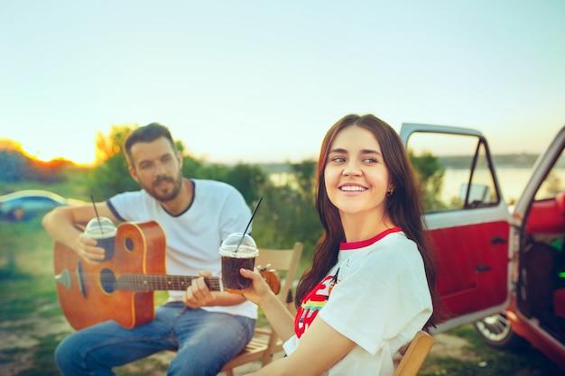 川の近くの夏の日にギターを弾いてビーチに座って休んでいるカップル。愛、幸せな家族、休暇、旅行、夏のコンセプト。