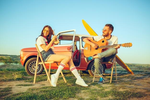 川の近くの夏の日にギターを弾いてビーチに座って休んでいるカップル
