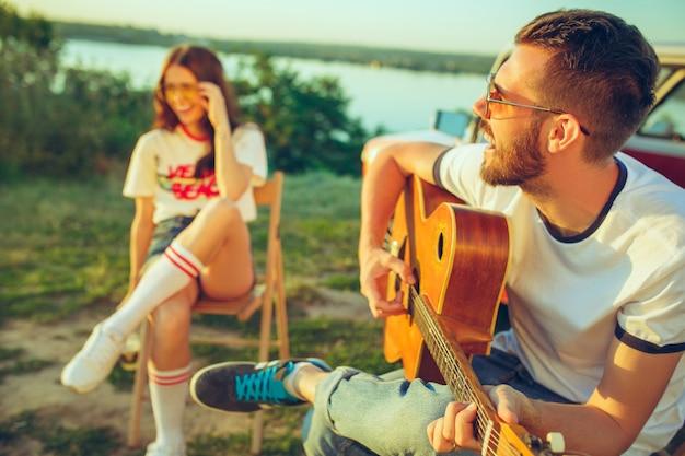 커플 앉아서 강 근처 여름 날에 기타를 연주하는 해변에서 휴식.
