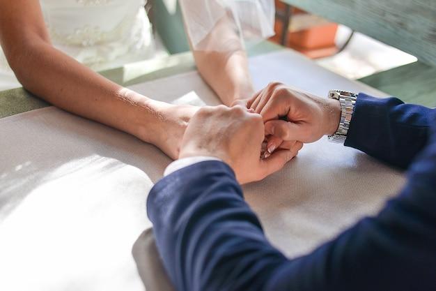카페의 테이블에 앉아 손을 잡고 있는 커플 신부와 신랑은 테이블에 앉아 손을 잡고 있습니다.