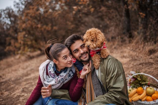 ピクニックに座って、犬と遊ぶカップル。