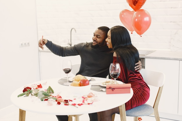 Пара сидит за столом, ест, разговаривает и смеется в день святого валентина