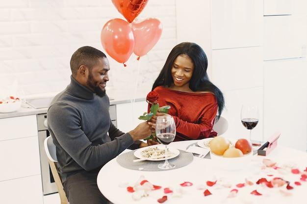 バレンタインデーにテーブルに座って、食事をし、話し、笑うカップル