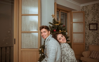 Couple sitting back to back near Christmas tree