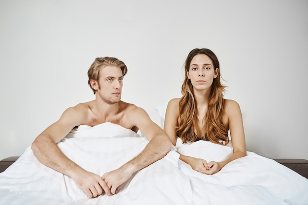 Couple sitting in bed under blanket having issues in bedroom expressing disappointment couple had fight in morning and moment of romance ruined. both do not want apologize first.