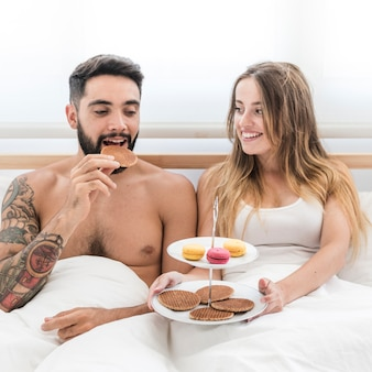 Couple sitting on bed having morning breakfast