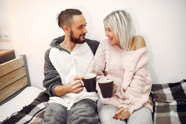 Couple sitting on a bed in a room drinking coffee