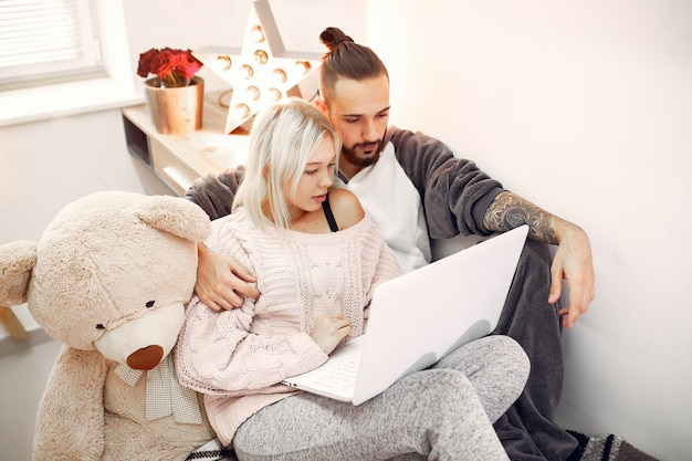 Couple sitting on a bed in a room and use a laptop
