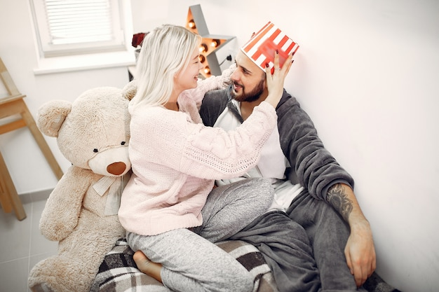 Couple sitting on a bed with big teddy bear and bucket of popcorn
