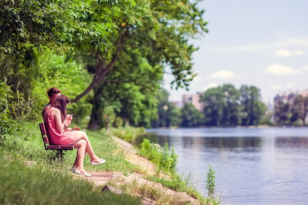 Couple sitting on a bench beside a lake on a sunny summer day