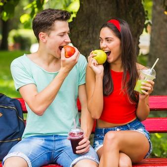 Coppie che si siedono sul banco che mangia le mele mature che tengono i frullati