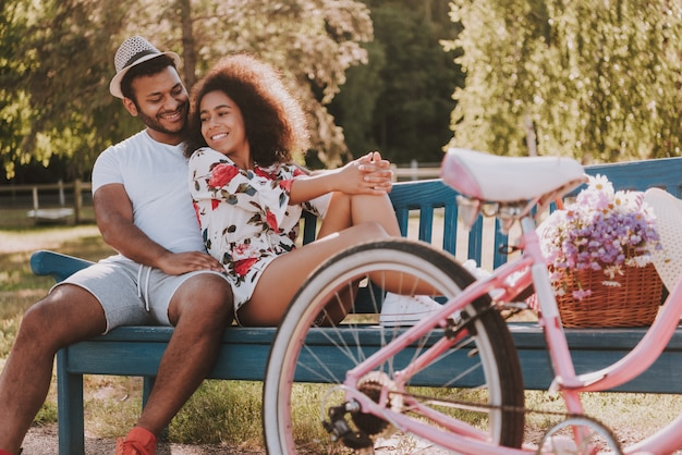 Couple sitting on bench in park bicycle date