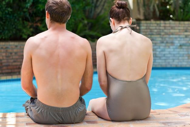 プールの横に座っているカップル