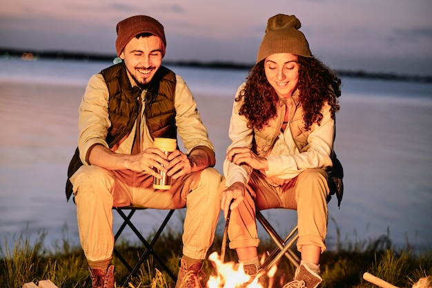Couple sitting at bonfire