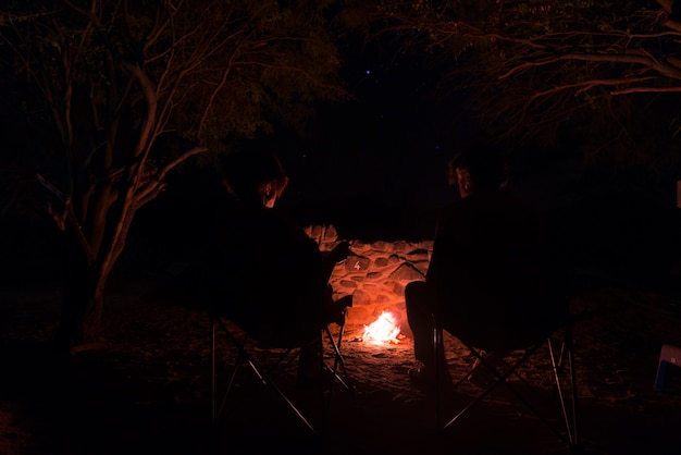 Couple sitting at burning camp fire in the night. namibia, africa. summer adventures