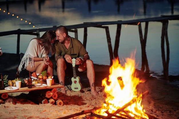 ビーチで火によって座っているカップル