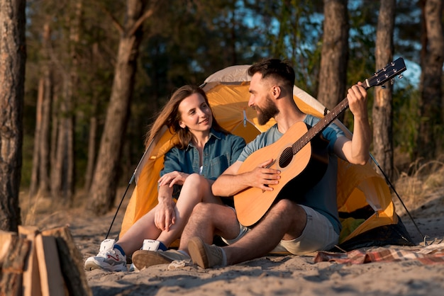 Couple sitting by the tent and singing