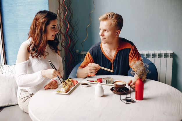 Couple sitting in a caffe and eating sushi