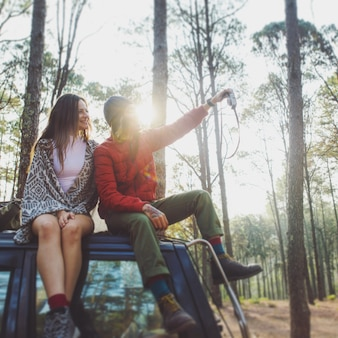 Couple sitting on a car roof in the woods