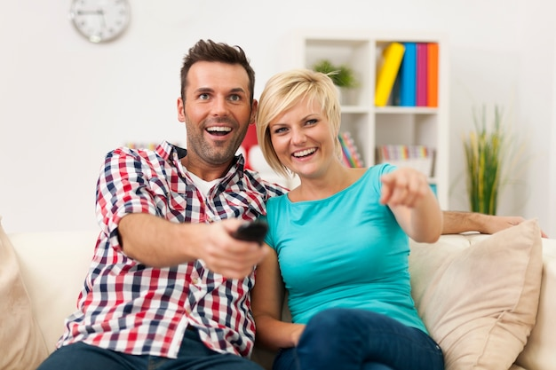 Couple sitting on couch and watching funny movie