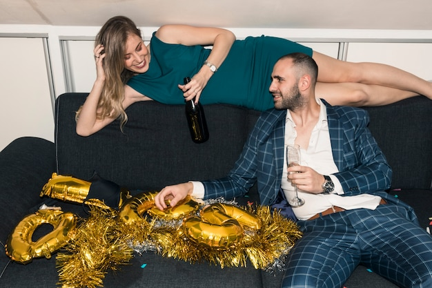 Couple sitting on couch with champagne on party