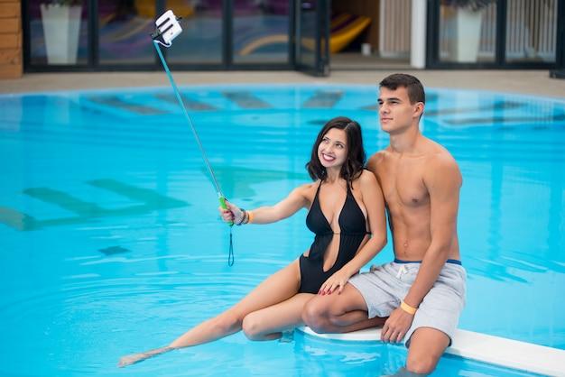 Couple sitting on edge of swimming pool