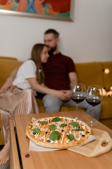 Couple sitting in an embrace on the couch. there is wine on the table. valentine's day date