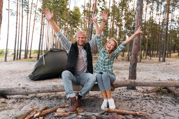 Couple sitting on a fallen tree with their hands in the air